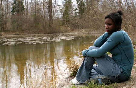 꽤 10 대 소녀가 연못 옆에 앉아.