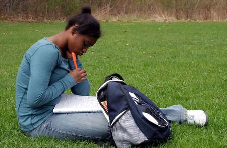 bookbag: A teenage girl doing homework. Stock Photo