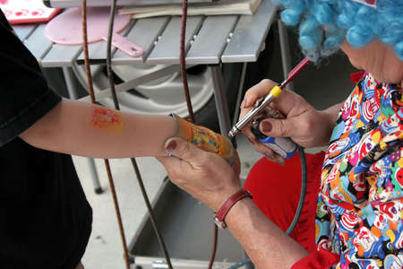 A child getting a tiger airbrushed onto his arm.