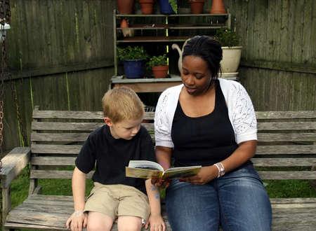 nanny: A boys sitter reading him a story. Stock Photo