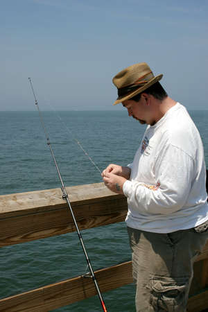 A man baiting a fishing hook on a fishing pier.