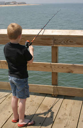 A little boy reeling in his fishing line. Stock fotó