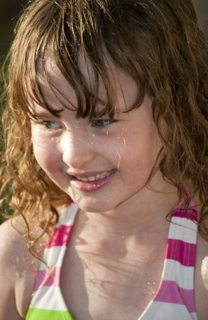 Girl playing outside with water on the summer photo