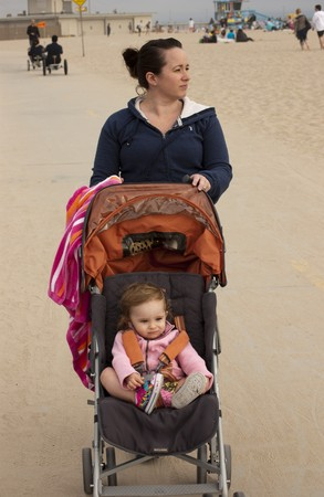 Woman pushing small child in stroller at the beach photo