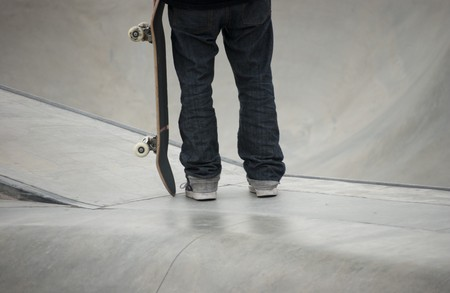 Teenager holding his skateboard at local skatepark Stock Photo - 7453055