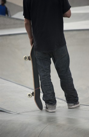 Teenager holding his skateboard at local skatepark Stock Photo - 7453041