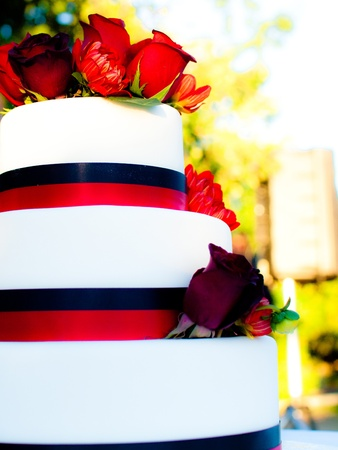 tier: A three tier cake deocated with flowers and ribbons