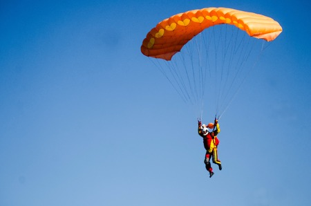 parachutists: parachutists come in the land on a beautiful orange parachute Stock Photo