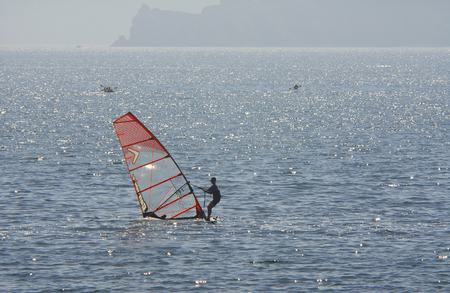 A man surfing without wind