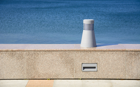 Lamp on the embankment against the blue sea