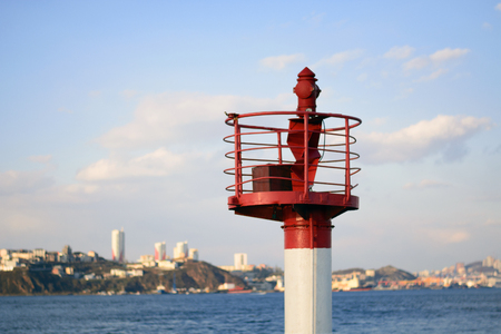 bright lighthouse on the background of the sea city