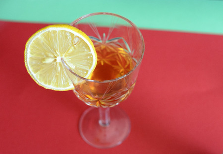 crystal wine glass with drink and lemon