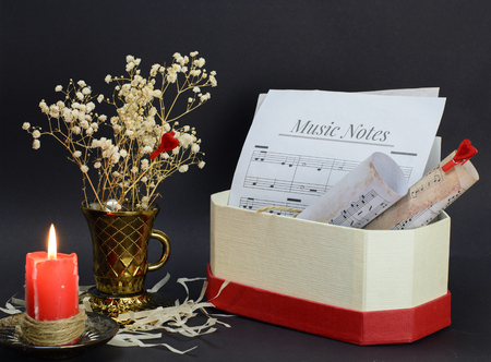 still life of a red candle, a vase of dry flowers and musical notes