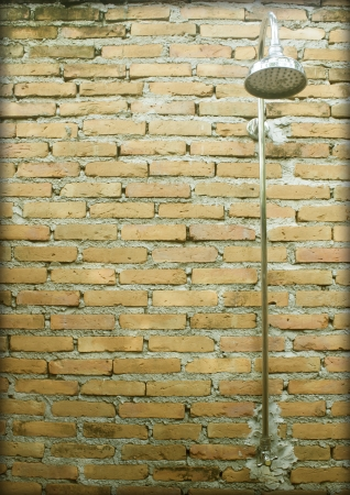 Head shower with old brick wall. photo