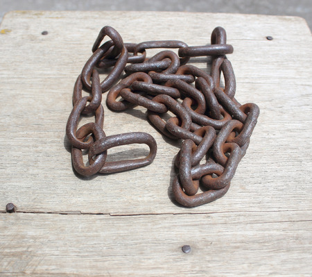 chandler: Rusty old steel chain on a wooden floor. Stock Photo