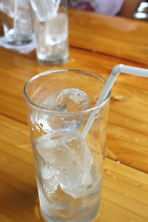 drunks: Glass with ice cubes on the table. Stock Photo