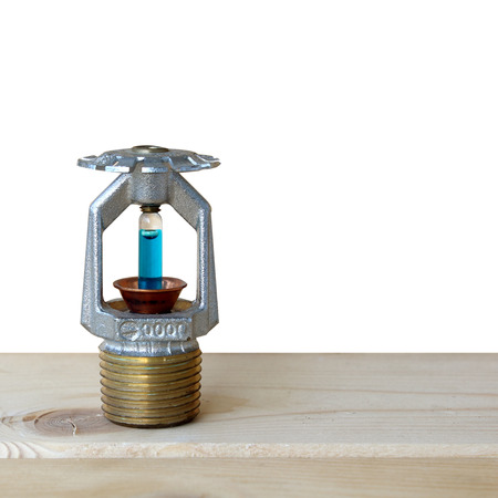 retardant: fire sprinkler with fire on wooden background.