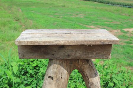 Wooden old table isolated on blurred green nature background.