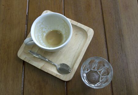 Empty coffee cup after drinking on wooden background.