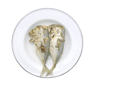 Two fried mackerel on a separate plate from a white background