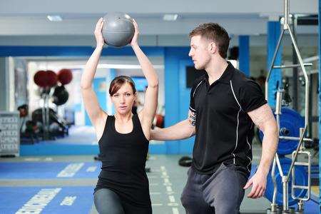 haciendo ejercicio: Entrenador personal ayudando a la mujer joven en el gimnasio Foto de archivo