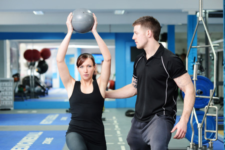 woman working out: Personal trainer helping young woman in gym Stock Photo