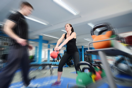 kettle: Young woman working out with kettle bell weights, with personal trainer in gym Stock Photo
