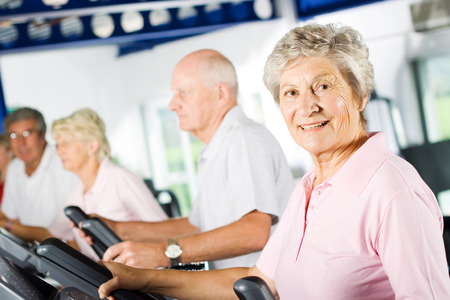 senior exercising: Group of older mature people exercising in the gym Stock Photo