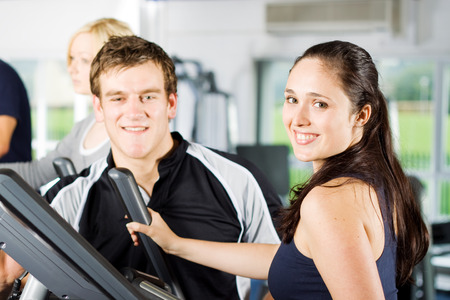 sports programme: Personal trainers in the gym giving instruction and help to attractive young women