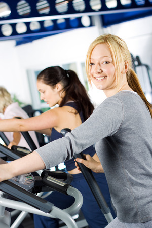 Attractive young blond girl working out with friends at the gym photo