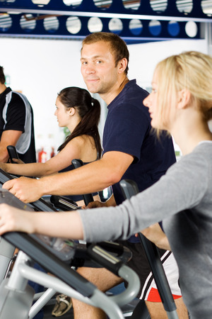 cardiovascular exercising: Handsome young man exercising in the gym with group of friends