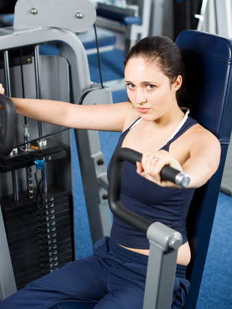 Attractive young girl working out at the gym photo