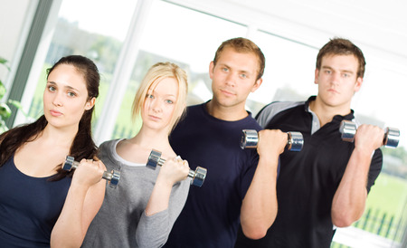 Group of young people lifting weights in the gym photo