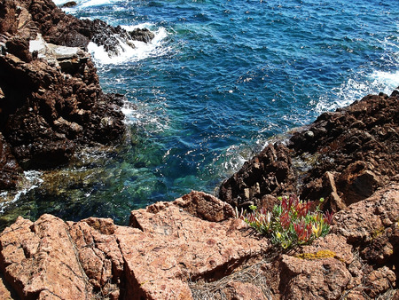 plunge: Flaming red rocks plunge into the deep blue sea impress imagination with the varying shades of green and blue change according to the weather.