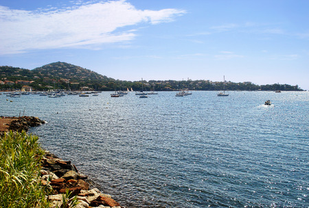 varying: Here you can find Esterel Corniche and  the extraordinary sight of the red Esterel rock plunging into the sea where the varying shades of green and blue change according to the seasons. The typical vegetation of the Mediterranean covers these hills. Stock Photo