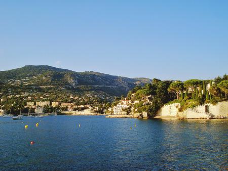 Cape Saint Jean Cap Ferrat Sea si trova tra due città Beaulieu-sur-Mer e Villefranche-sur-Mer. Costa rocciosa di Saint Jean Cap Ferrat capo è molto bella. Al tramonto corone verdi di alberi ottenere una morbida tonalità dorata. Archivio Fotografico - 39388444