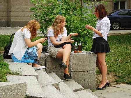jeune fille adolescente nue: Trois jeunes filles sont assis sur les marches de l'échelle dans le parc de la ville, boire de la bière et de parler. Les problèmes sociaux, les intérêts de la jeune génération, la culture publique