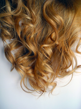 permanent wave: Womens ringlets of color amaretto gold close-up.