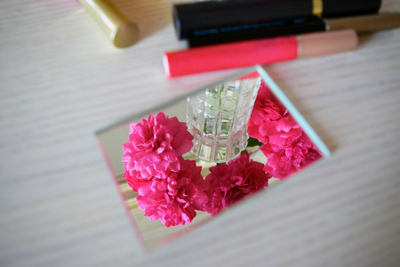 dressing table: Cosmetics and flowers on the female dressing table. Stock Photo