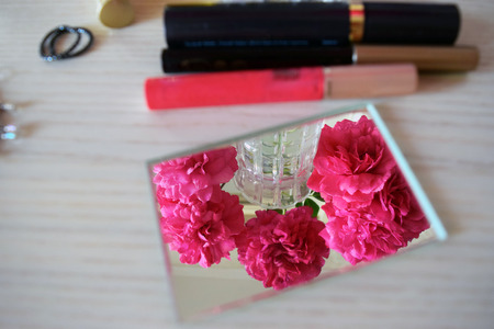 Cosmetics and flowers on the female dressing table. Stock Photo