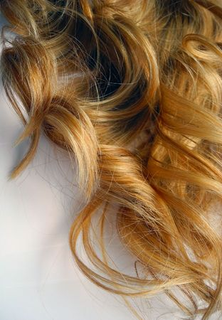 Womens ringlets of color amaretto gold close-up.