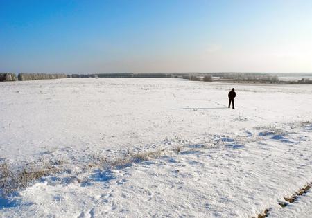 snowy field: Lonely boy in snowy field in winter.