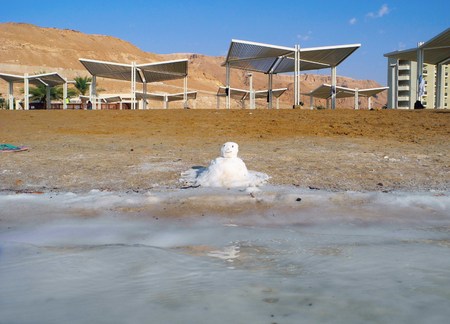 recuperation: Salt snowman on the hot beach of Dead Sea in Israel. Stock Photo