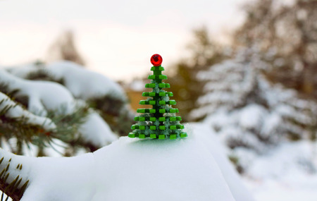 The little snowy toy Christmas tree on the winter landscape background.