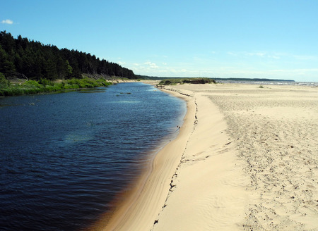 The sandy Baltic beach, the river flows into the sea.