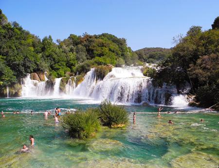 Krka National Park, Croatia - July 7, 2016: Visitors taking a bath at waterfall Skradinski Buk.