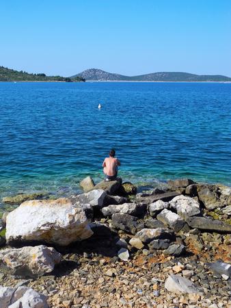 dalmatia: The boy sat down on stone on the coast of Adriatic Sea in Croatia. Stock Photo