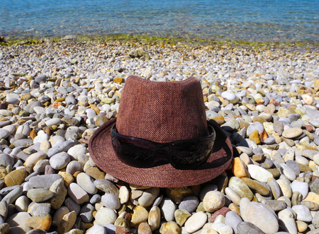 Hat and sunglasses on the pebble beach of the Adriatic.