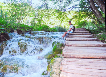 admire: The man on the footpath near a waterfall.