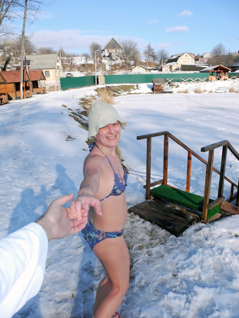 The woman after a sauna going dip in the ice-hole. Stock Photo